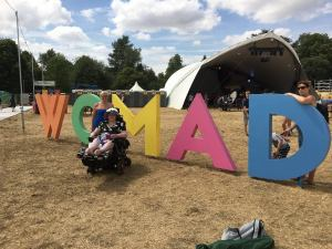 Lucy in front of WOMAD sign