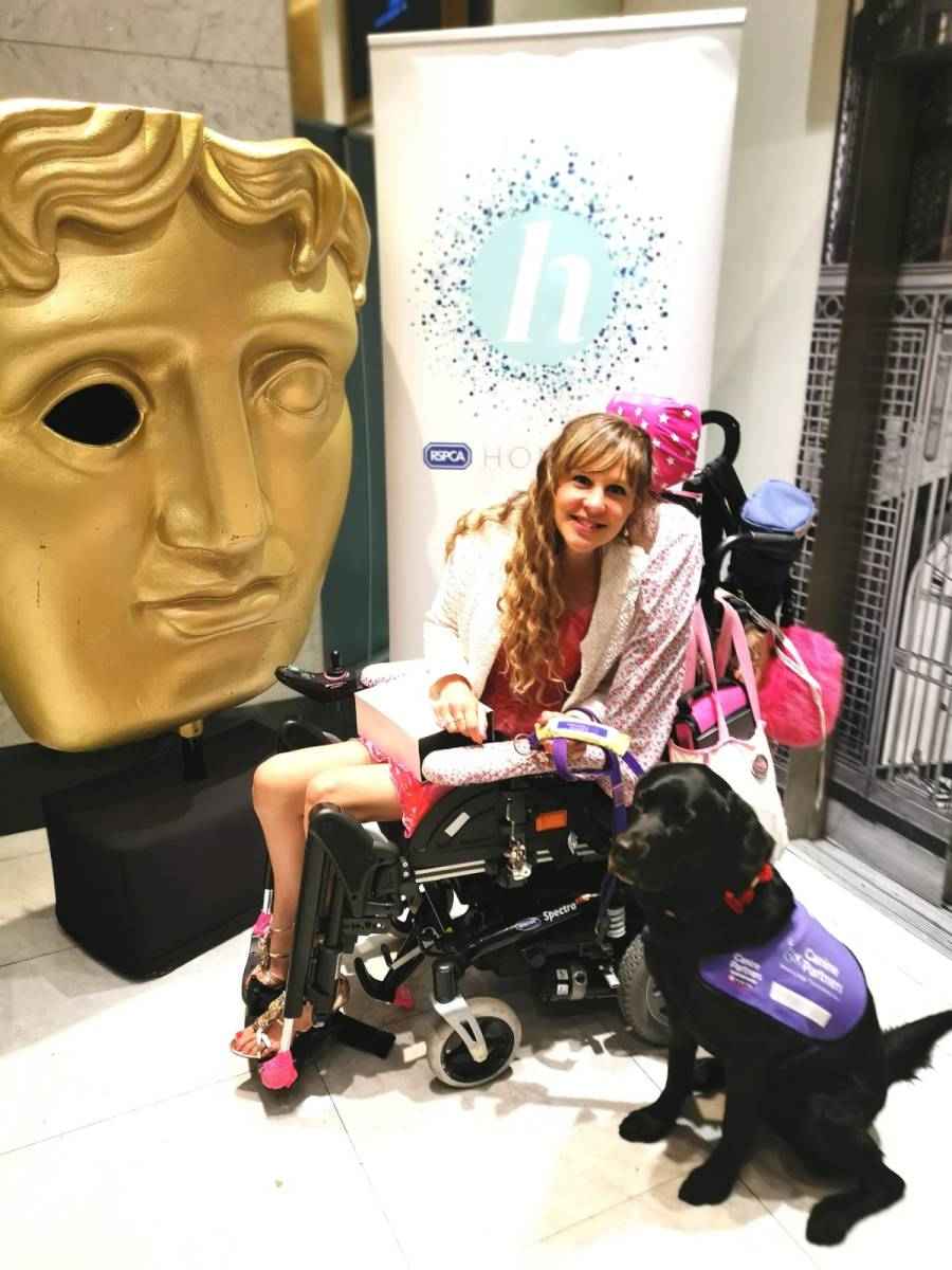 Sally posing with Ethan next to a Bafta statue